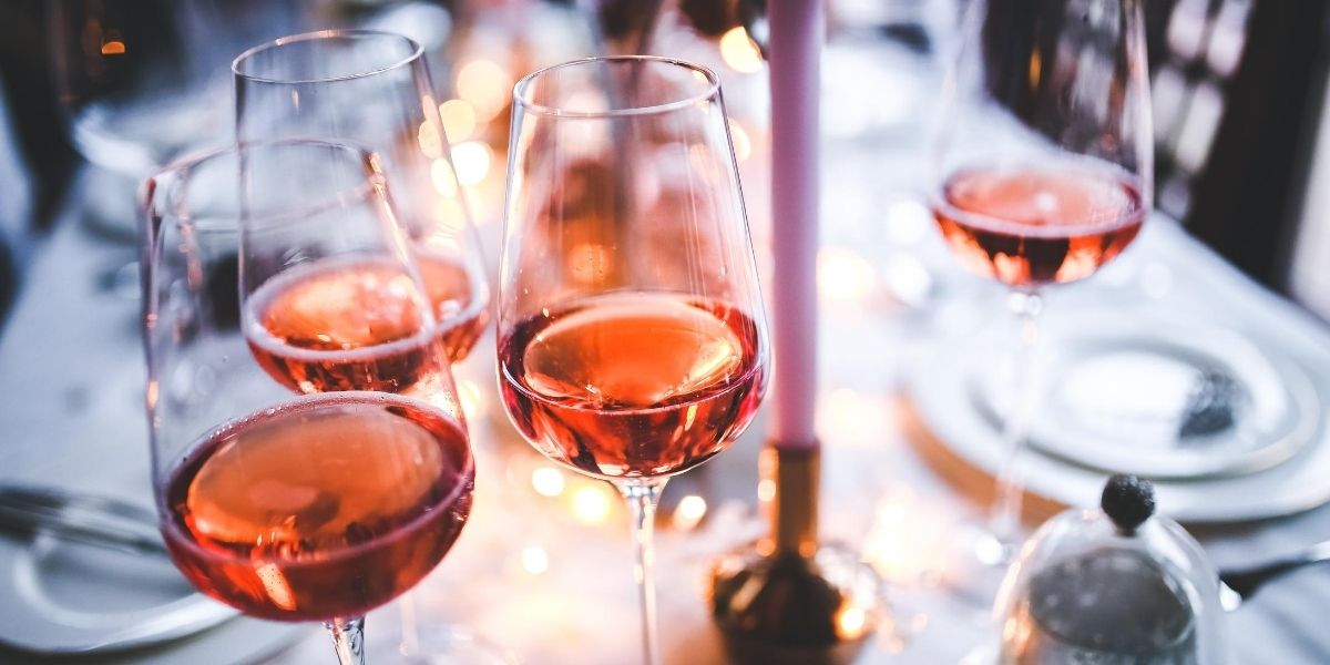 Sweet pink wines poured in wine glasses on a dinner table